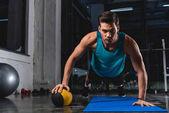 Fotografia sportivo muscolare facendo push ups con palla medica sulla stuoia di yoga nel centro sportivo