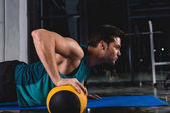 Fotografia Sportsman facendo push ups con palla medica sulla stuoia nel Palazzetto dello sport
