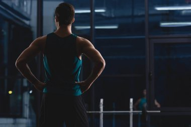back view of silhouette of muscular sportsman standing in sports center