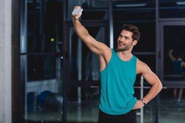 smiling sportsman taking selfie on smartphone in gym