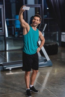 cheerful sportsman taking selfie on smartphone in gym with treadmill