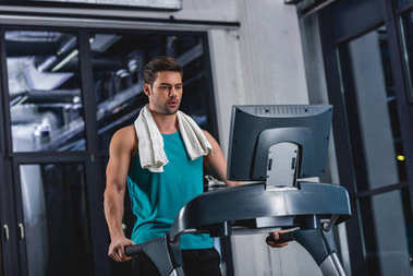 tired sportsman with towel exercising on treadmill in sports center