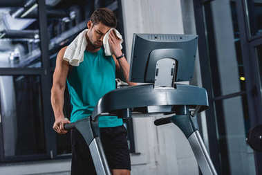 tired sweaty sportsman with towel training on treadmill in gym