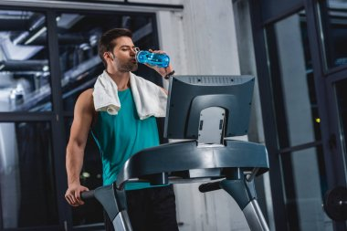 tired sportsman with towel drinking water while training on treadmill in gym