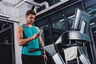 sportsman listening music with earphones and smartphone while training on treadmill in gym