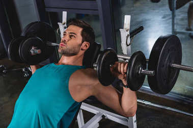 muscular sporty man exercising with dumbbells in gym