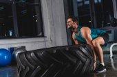 Fotografie sportovec, zvedání pneumatik během cross trénink v tělocvičně