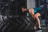sportovec, zvedání pneumatik během cross trénink ve sportovním centru