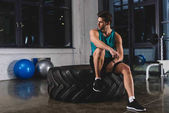 sportsman sitting on tire in sports center