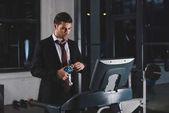 podnikatel v obleku školení o běžecký pás s lahví vody v sportovním centru