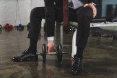 oříznutý pohled sportovní podnikatel v obleku školení s činka v posilovně