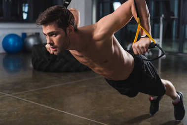 shirtless sportsman training with elastics in sports hall