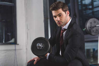 handsome businessman in suit training with dumbbell in sports center