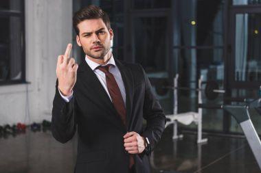 businessman in formal wear showing middle finger in sports center