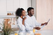 Fotografie Smiling african american man reading newspaper while girlfriend embracing him  in kitchen