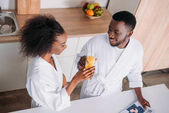 High angle view of couple clinking with glasses of orange juice in morning