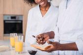 Oříznutý pohled mladého muže šíření jam na toastu a usmívající se holka poblíž