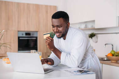 Smiling man doing online shopping and standing with credit card in kitchen