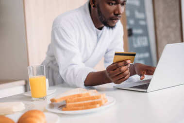 Cropped view of african american man with credit card doing online shopping