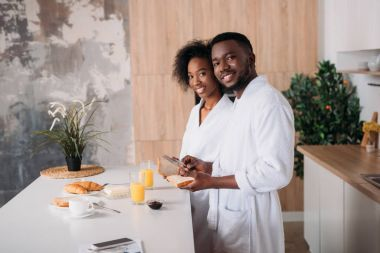 Smiling african american couple having breakfast in kitchen
