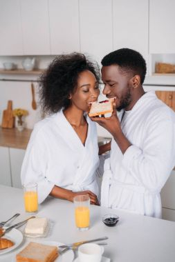 African american couple eating toast with jam in kitchen