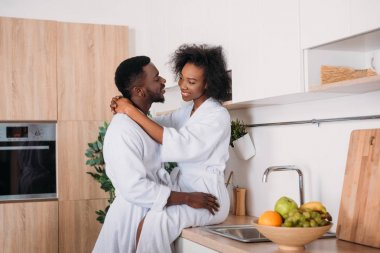 Smiling african american couple hugging in kitchen stock vector