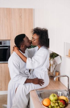 Side view of african american couple kissing in kitchen stock vector