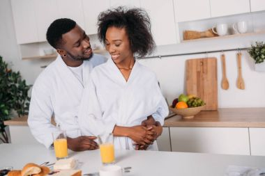 Young man embracing smiling girlfriend while standing at table with breakfast in kitchen