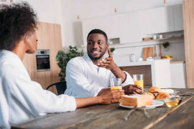 Smiling african american man talking to girlfriend while sitting at table with breakfast
