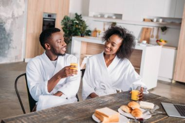 Smiling couple sitting at table with breakfast and laptop in kitchen
