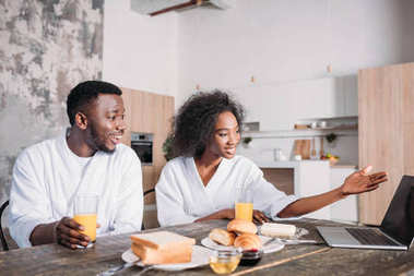 Young african american couple sitting at table with laptop and breakfast