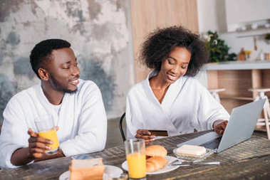 African american couple having breakfast and doing online shopping in kitchen