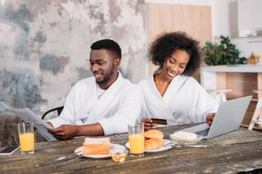 African american man having breakfast with girlfriend doing online shopping in kitchen