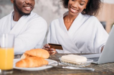 Cropped image of young smiling couple having breakfast and doing online shopping with credit card