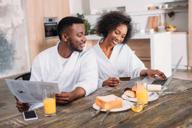 Young man with newspaper and smiling girlfriend with credit card doing online shopping