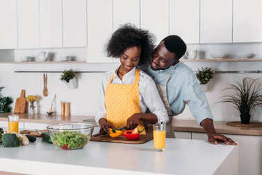 Smiling man hugging girlfriend while she cutting pepper on board in kitchen