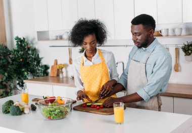 Young couple in aprons cutting vegetables on board in kitchen