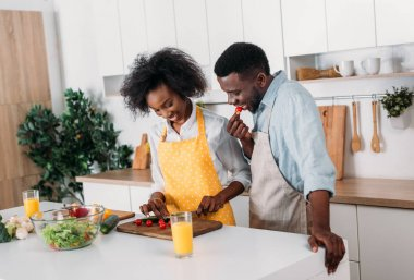Smiling couple in aprons cutting vegetables on board