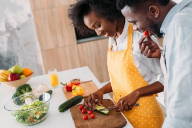 Young woman cutting cucumber on board and boyfriend eating cherry tomato