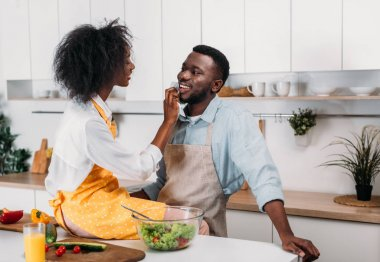Young african american wiping mouth of boyfriend by napkin