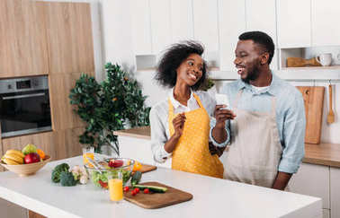 African american couple in aprons standing at table with food and using smartphone in kitchen