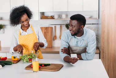 Woman mixing salad in bowl at table and boyfriend standing with smartphone in hand