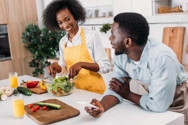 Young woman mixing salad in bowl at table and boyfriend standing with smartphone in hand