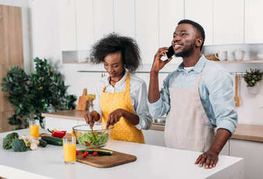 Woman mixing salad and boyfriend talking on smartphone in kitchen