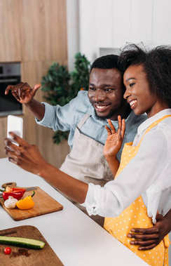 Young african american couple in aprons taking selfie in kitchen