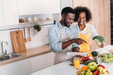African american couple looking at recipe on digital tablet while standing at table with vegetables