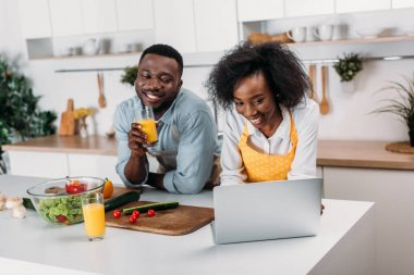 African american couple having fun with laptop in kitchen