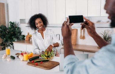 Cropped image of man taking photo of girlfriend with hand in salad