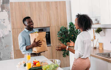 Young african american man bringing paper bag with products while girlfriend standing in kitchen