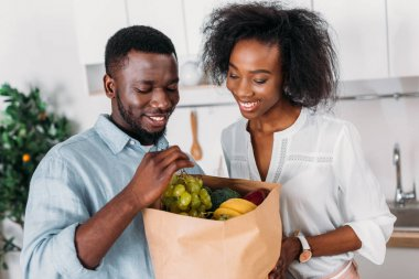 Young african american couple holding paper bag with grapes and bananas